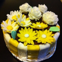 Flower Pot Moist Yellow cake with chocolate frosting . All the flowers are made from marshmellow fondant.