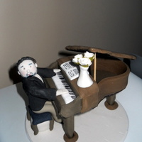 "Piano Man   This is a little man and piano made entirely from icing. It sits on a 6"" iced plaque board. I made it for a mans birthday cake."