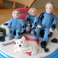 "Mechanics This topper is on a 6"" iced board with hand made figures of the Daddy and his two boys and their dog. They are all made from icing."