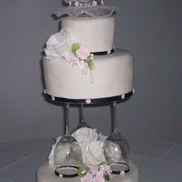 Wine Glass Tiered Wedding Cake  The cake is french vanilla with strawberry filling, covered with a layer of buttercream and Satin Ice fondant. The white flowers are silk,...