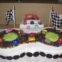 Lightning Mcqueen Racetrack two 10 inch round cakes iced with buttercream. Crushed oreos for the road and oreos around the bottom. The grandstand is made out of rice...