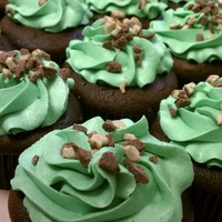 Shamrock Cupcakes Chocolate fudge cake topped with mint buttercream with chocolate mint crumbles.