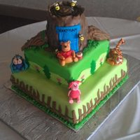 Winnie The Pooh Cake This a a winnie the pooh cake. The tree is RCT covered in fondant. The remainder is cake covered in butter creams and fondant detail. The...