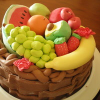 A Basket Of Fruits A white cake filled with mango filling. Cake is covered in fondant and fruits are made out of gumpaste.