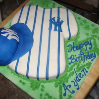 Aydens Ny Cake  Made for nephews 2nd bday. Used the tshirt pan for the jersey. Used the sports ball pan for the hat. Buttecreamed and then MMF. The blue is...