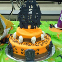Haunted House 2 Tier yellow vanilla cake with strawberry filling bottom tier and Nutella filling top tier; fondant coveing, chocolate skulls and tombstones and...