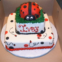 "Lady Bug   10"" and 6"" strawberry cakes stacked with BC and MMF. Lady bug is built with cupcakes. Little Ivey's 3rd b Day"