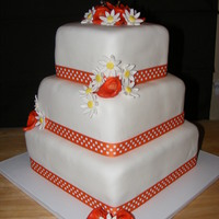 Tn Vols Themed Wedding Cake 6, 8 and 10 in square covered in white fondant. orange calla lily and daisies made from fondant. Bride wanted the polka dot ribbon around...