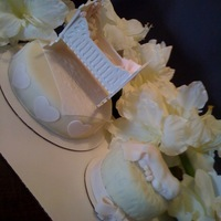 Baby Shower Cakes white chocolate cradle with fondant accents and a sleeping baby. Pale pink and ivory cake.