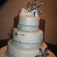 Christmas Wedding Cake white fondant wedding cake with eggless top tier due to groom having egg allergy. cake covered in luster dust and wrapped in ribbon with...