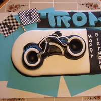 Tron Cake Cake covered with rolled and MMF. Light Cycle made from RKT covered with True Black MMF and accents with rolled fondant. TRON logo is RKT...