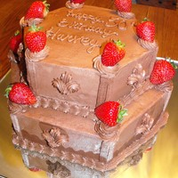 Strawberry Bliss 2 tier hexagon shape cake with chocolate frosting......accented with chocolate fleur-de-lis on each side with shell border piped on each...