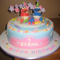 Sesame Street Girls Cake This was made for a little girls birthday - in a girlie theme for sesame street. figurines are all hand carved chocolate, gumpaste flowers...