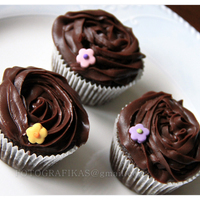 Chocolate Cupcakes Frosted With Ganache   Chocolate cupcakes with ganache frosting. Decorated with little fondant cutouts.