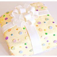 It's A Present, It's A Cake A birthday cake made of white almond sour cream. For the bow and colorful dots, I used fondant and gum paste.