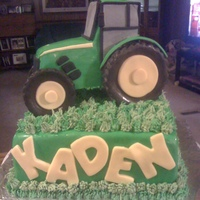 Tractor Cake A tractor cake for a little boy's 2nd birthday. The tractor is made of cake, covered in fondant. The grass is buttercream. The cake is...