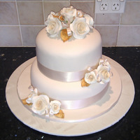 Ivory And Gold Wedding Cake Ivory fondant covered cakes, with moulded roses tinted with cream calks and gold painted leaves. Ivory ribbon detail. Top cake is...
