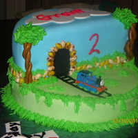 "Thomas The Train   Vanilla cake with fondant figures. ""Rocks"" are Jelly Beans, attached with chocolate."