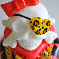 Girly Skull Cake Strawberry cake with cream cheese frosting, fondant decorations, cereal treat and fondant skull.