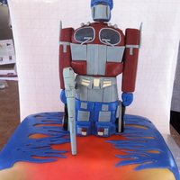 Optimus Prime - Transformers Vanilla base with buttercream icing. Rice cereal Optimus Prime structure. The details are made of fondant, gumpaste and modelling chocolate...