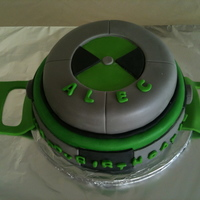 "Ben 10's Watch, Omnitrix 10"" and 8"" Chocolate cakes covered with fondant layered with whipped cream."