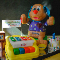My 1St Fondant Cake - My Son's 1 Yr Birthday  vanilla cake covered in marshmallow fondant. Piano and blocks are all cake, the head and paws of the dog are rice krispy, body is cake. The...