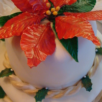Gumpaste Poinsettia Two tiered white fondant cake topped with a gumpaste poinsettia. Each layer is adorned with a monochromatic fondant rope brushed with gold...