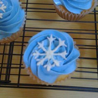 Winter Cupcakes :) Lemon cupcakes filled with raspberry jam. Topped with vanilla Swiss meringue butter cream. Snowflake was made with wilton white candy melts...