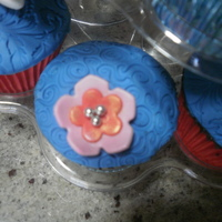 Blue Cupcakes With Flowers   For mermaid themed party, blue fondant, pink flowers and frangipanis, also a few buttercream swirls