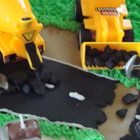 Construction Themed Babyshower Cake! road is made of Black fondant and I rolled individual balls to make it look like asphalt was coming out of the truck and to make it look...