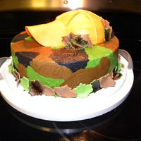 Camo Cake Yellow cake dyed green, black, and tan to look like camo! Frosted with buttercream fosting. The leaves and hat bill are made from a fondant...