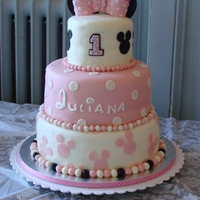 "Minnie Mouse Themed 1St Birthday 6, 10 and 12"" Tiers of Vanilla cake filled with chocolate mousse and covered with MMF. Cupcakes are all vanilla with vanilla..."