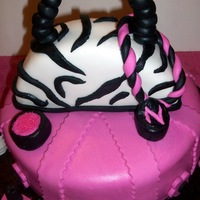 Zebra Purse Fondant Cake This is a 10 inch round fondant covered cake and the cake was made out of a 8 inch round. This cake was made for a birthday.