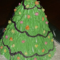 Christmas Tree Made with Giant Cupcake pan and then sculpted to look like a tree. Frosted with Buttercream. Gel decorating icing used for Garland. Mini...