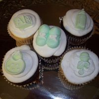 Green Baby Toppers cupcakes with fondant molded toppers and buttercream baby booties