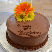Chocolate Birthday Cake   Chocolate cake with chocolate buttercream icing. Fresh flowers for decoration on top.