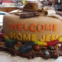 Indiana Jones Welcome home cake for a friend. Hat and whip made from fondant, Golden coins are bought chocolates in foil. Snakes are gummy candy.
