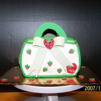 Strawberry Short Cake Purse   2 loaf pans, buttercream icing, fondant/gumpaste accents for a 2 year old. The 2 year could care less, the mom loved it.
