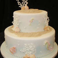 Two Tier Ocean Theme Wedding Cake This two tier Ocean themed wedding cake is decorated with hand piped coral, fondant shells and Sea Horses, piped pearls and edible sand. It...