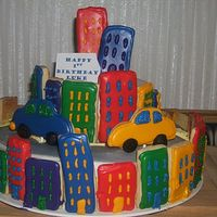 Crazy City Cake Looked a bit off- but tasted great. Sugar cookie buildings and cars, fondant road. My first time with color flow. I got impatient and just...