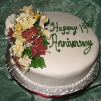 Img_1910.jpg This is a Jamaican Fruit cake covered with fondant and decorated with gum paste flowers.
