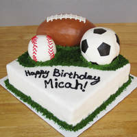 Sports Themed Cake The balls are made of rice treats and covered in fondant. Grass is buttercream icing. I desperately need to work on my penmanship on cakes...