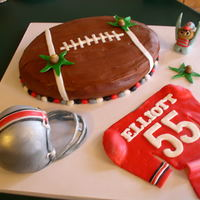 Go Team birthday cake - football is choc cake with fudge frosting, helmet is white cake with mm fondant, jersey and brutus are mm fondant. the...