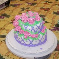Two Tiered Flower Cake  Fondant covered tiered cake, with fondant roses and fondant ribbon roses on the cake. Purple dots in buttercream icing surrond the whole...