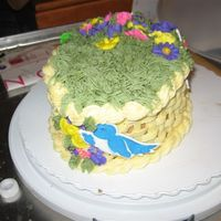 Basket Flower Cake Oval cake with chocolate butter cream, the basket weave in ivory, green moss on top and the flowers set in