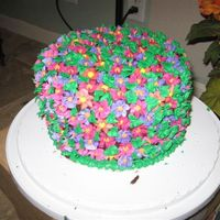 Flower Cake Flowers individually made with Royal icing and put on the cake all around, used leaf tip to do the leaves