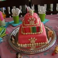 Pretty Little Puppies Three sqaure tiered cake covered in pink fondant and bright colored fondant stripes with doggie paw prints and cute little gumpaste puppy...