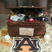 Toy Box Cake My customer requested a toy box with specific items spilling out. Chocolate cake with chocolate fondant. All edible decorations. The cars...