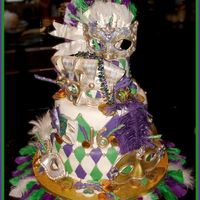 Mardigras2.jpg  Cake is covered in fondx and the masks and fan are gumpaste. The coins are the chocolate foil covered kind. This was my absolute fav cake...