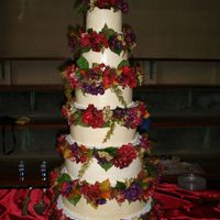 Sara.jpg This wedding cake was assembled using the tall tier stand and silk flowers provided by the bride. The layers were sizes 6-16 in two inch...